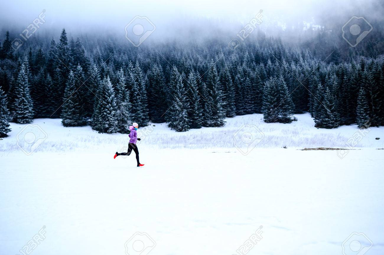 Sport, fitness inspiration and motivation. Young happy woman cross country running in mountains on snow, winter day. Female trail runner jogging exercising outdoors. - 43899694