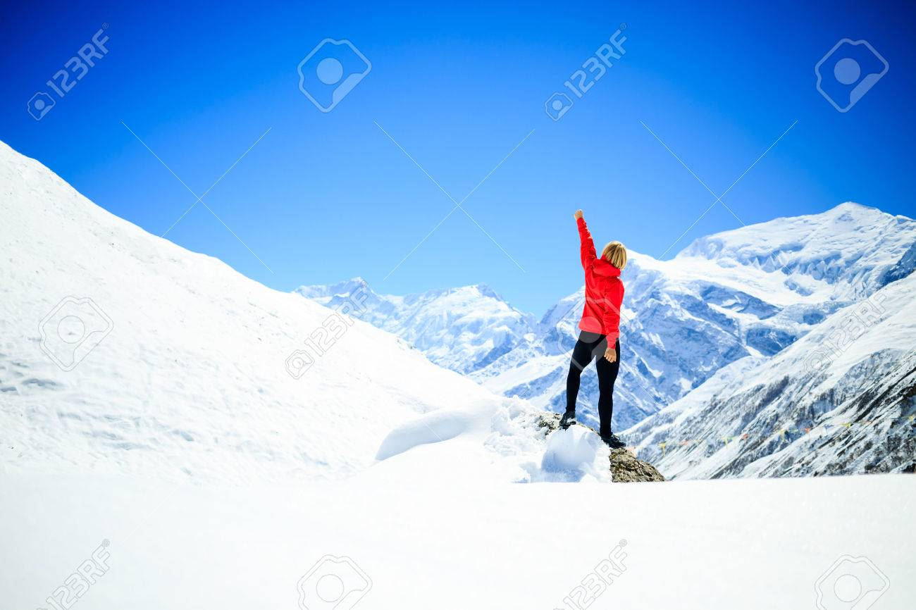 Young happy woman hiker successful on mountain peak summit in winter mountains. Climbing inspiration and motivation, beautiful landscape. Fitness healthy lifestyle outdoors on snow in Himalayas, Nepal. - 45775471