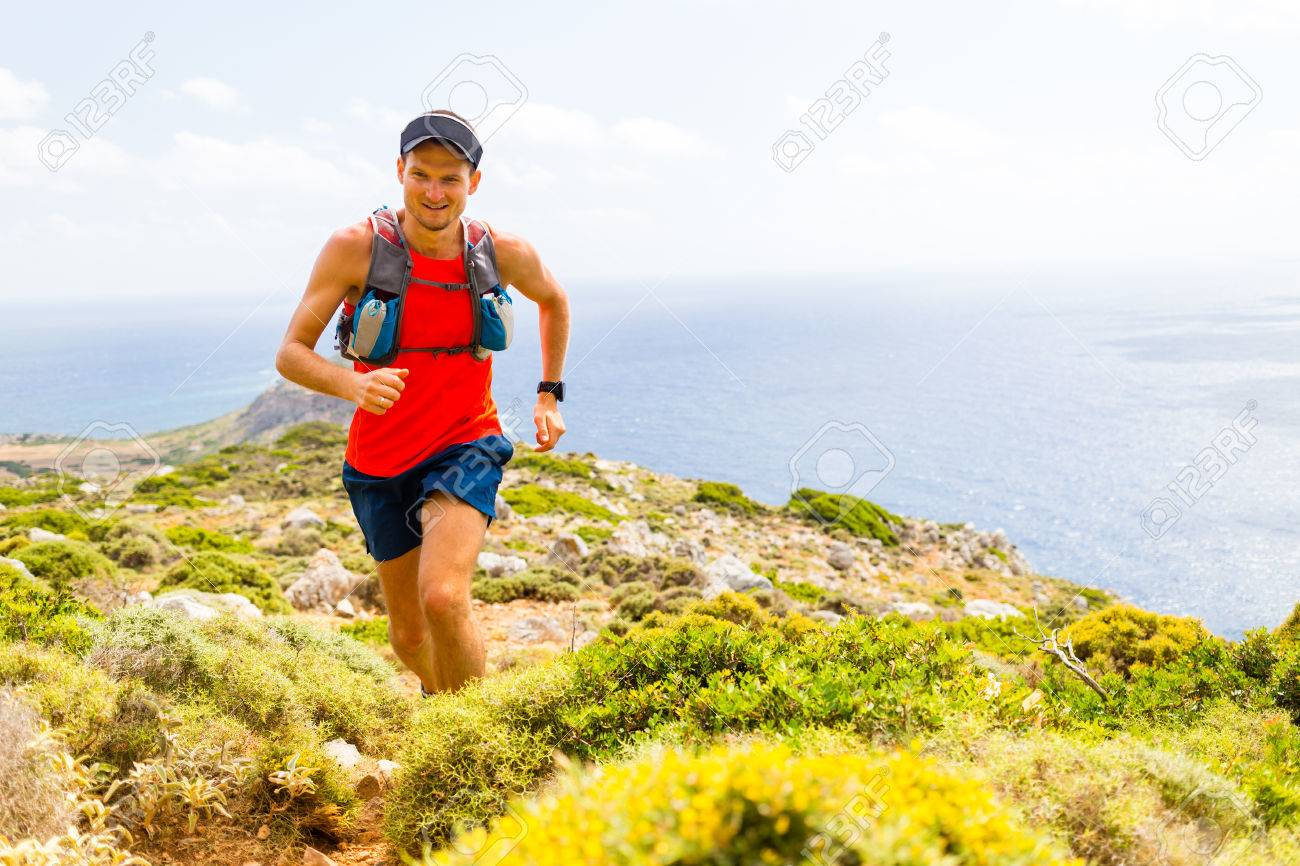 Trail running man, happy cross country runner in inspirational mountains landscape on beautiful day. Training and working out person jogging and exercising outdoors in nature, rocky footpath on Crete, Greece - 45886341
