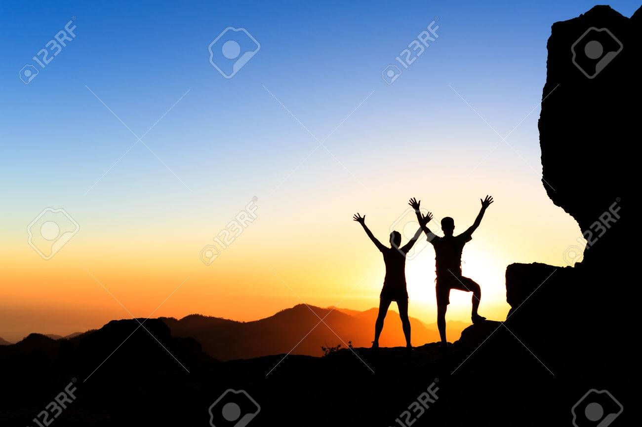 Couple hikers success in sunset mountains, accomplish with arms up outstretched. Young man and woman on rocky mountain range looking at beautiful inspirational landscape view, Gran Canaria Canary Islands. - 46613359