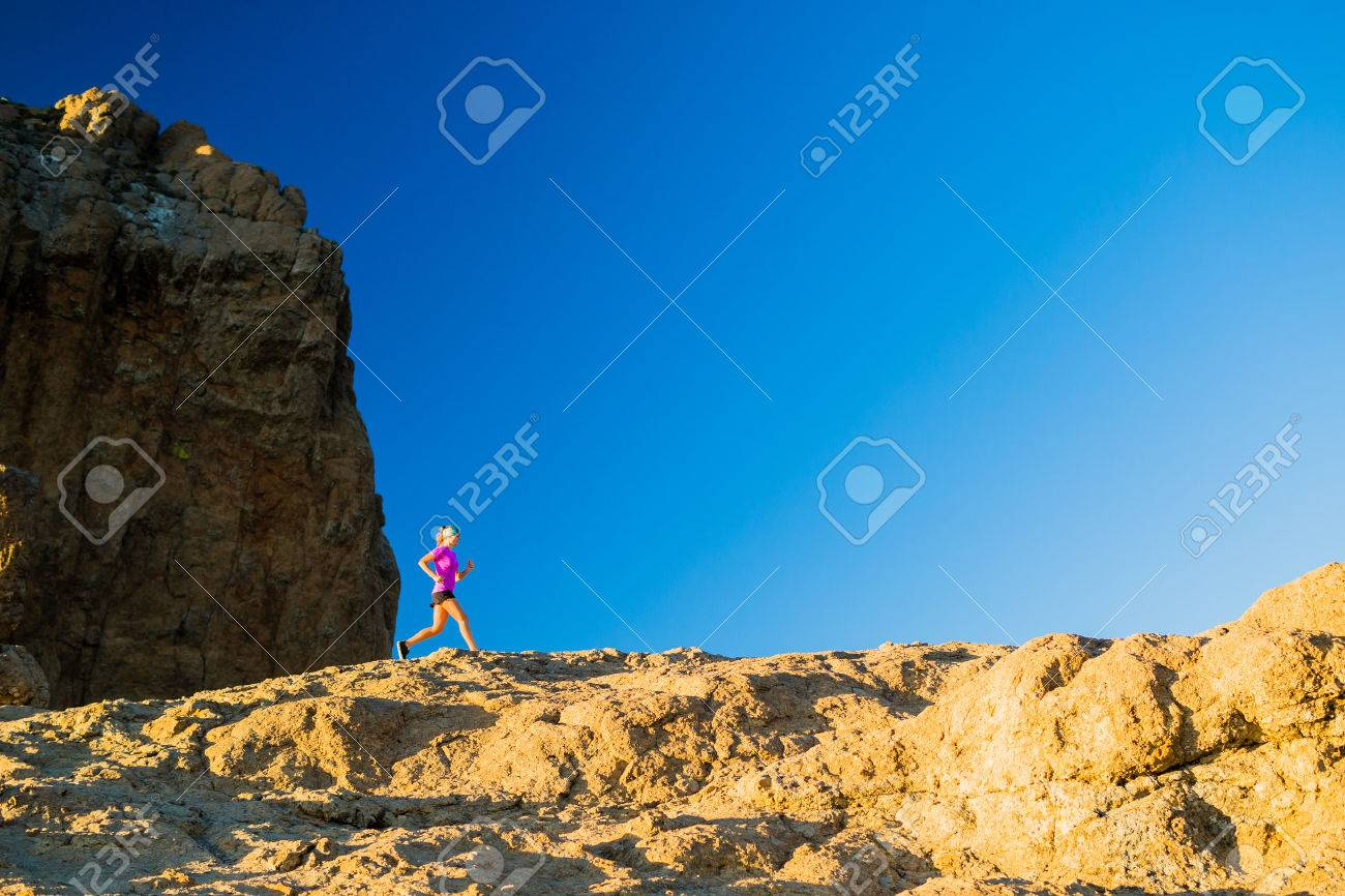 Woman running on rocky mountains, training and working out in beautiful inspirational mountain landscape. Fitness and exercising, cross country runner jogging. - 46613389