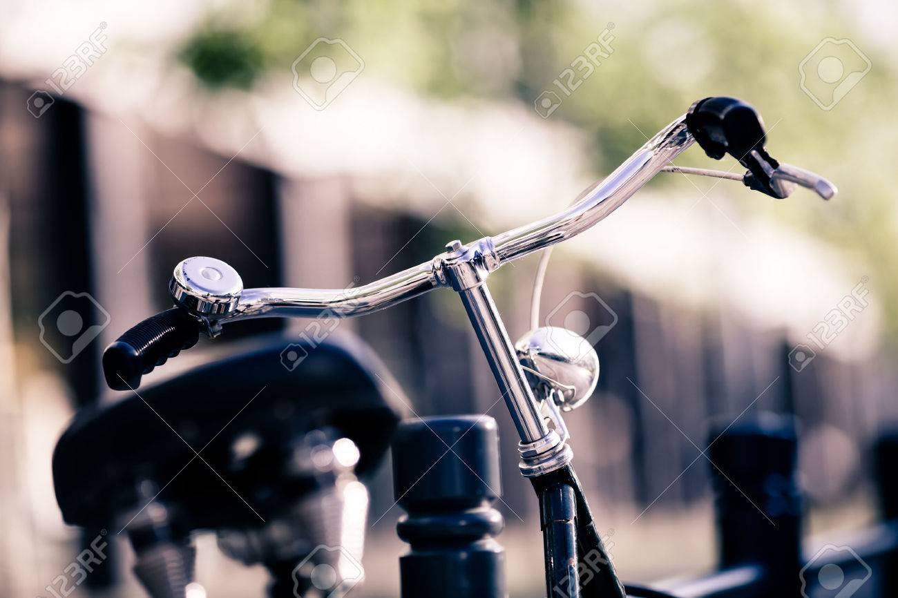 Vintage old city bike colorful retro light and handlebar on street, alternative ecology transportation, commute on classic bicycle in urban environment, blurred beautiful bokeh background. Selective focus on handlebar. - 47322800