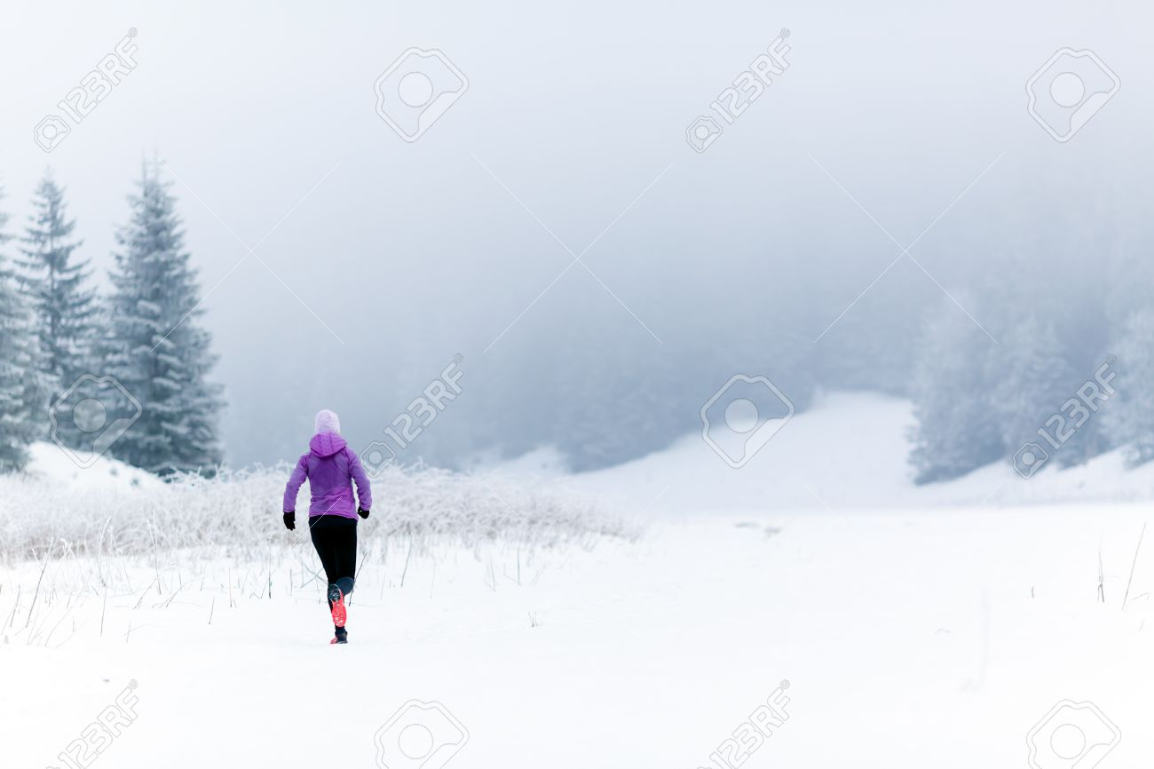 Winter running woman. Sport, fitness, jogging inspiration and motivation. Young happy woman cross country running in mountains on snow, winter day. Female trail runner working out, jogging exercising. - 47628865