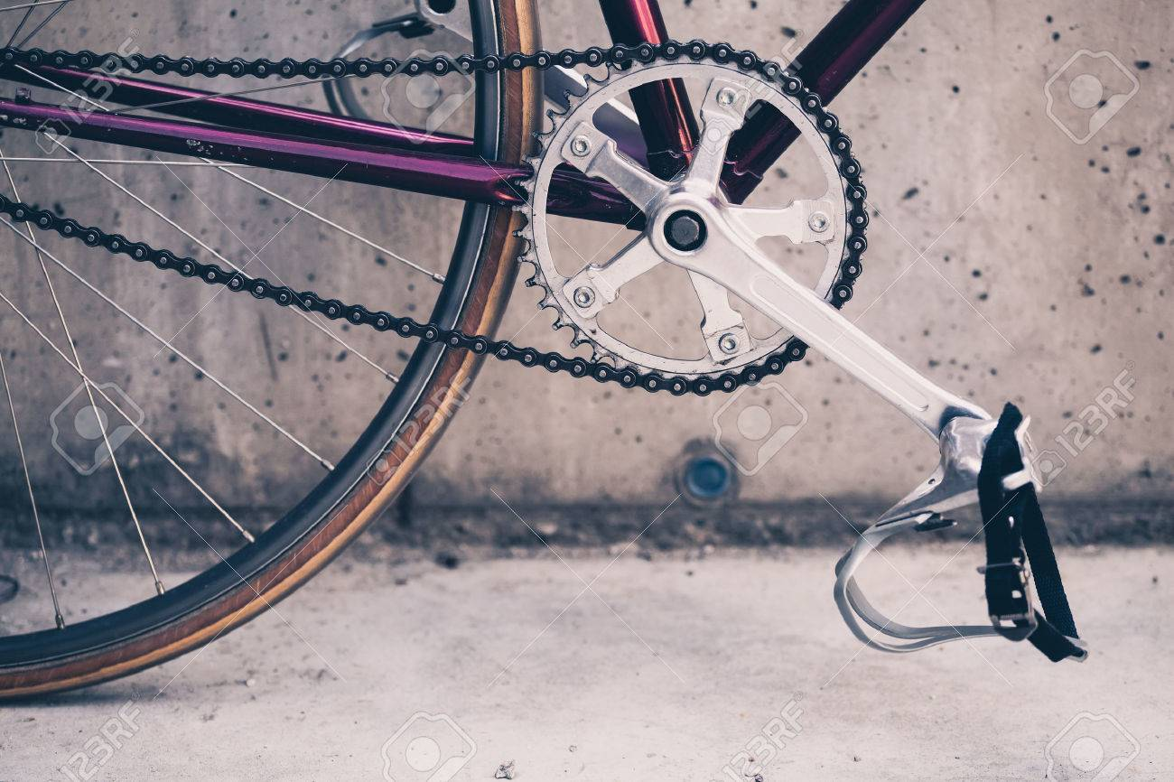 Road bicycle, fixed gear bike on city concrete street. Urban industrial cycling, bike chain on city scene bicycle closeup details, vintage old retro bike, cycling or ecology commuting. Industrial concept. - 49021306