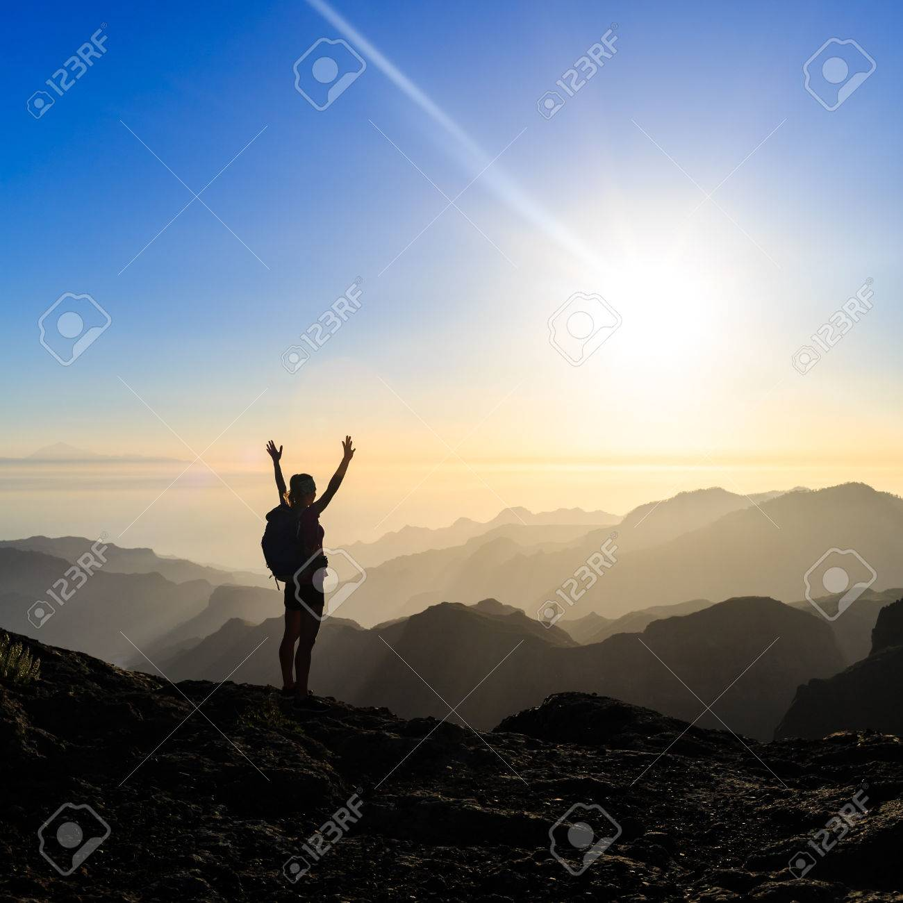 Woman successful hiking climbing silhouette in mountains, motivation and inspiration in beautiful sunset and ocean. Female hiker with arms up outstretched on mountain top looking at beautiful night sunset inspirational landscape. - 49609434