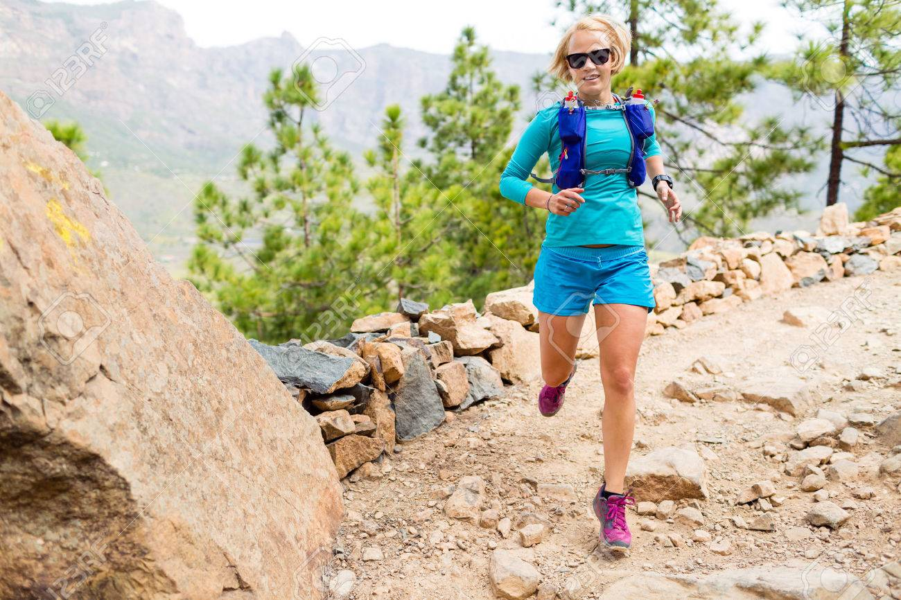 Trail runner woman cross country running in mountains, inspirational landscape. Training and working out runner jogging and enjoy outdoors in nature, rocky footpath on Canary Islands, Spain - 52377482