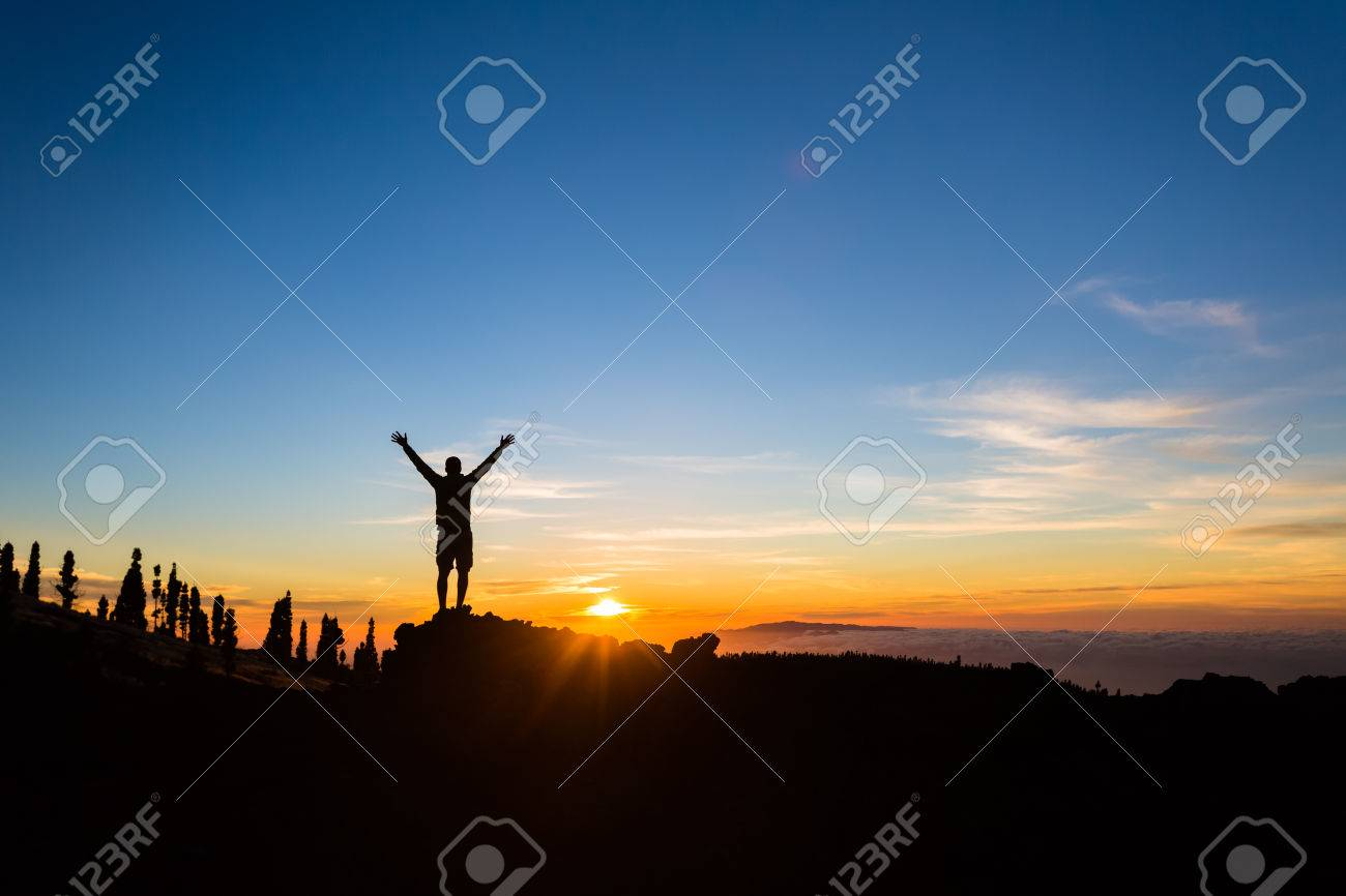 Man hiker silhouette with arms outstretched in mountains. Male runner or climber looking at sunset view. Business concept and hands up and enjoy inspirational landscape, rocky trail footpath on Tenerife, Canary Islands - 56096654