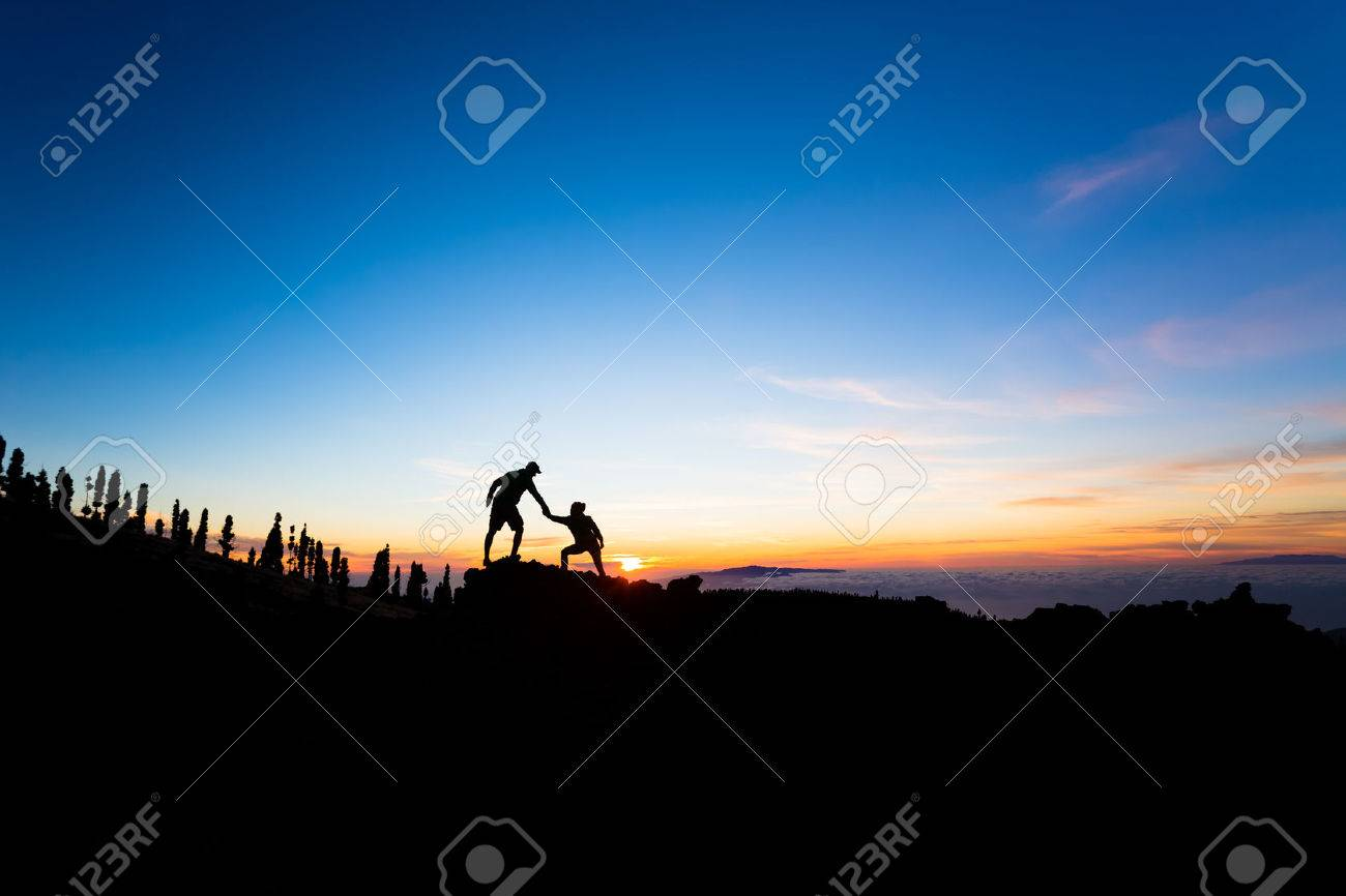 Teamwork couple helping hand trust help silhouette in mountains, sunset. Team of climbers man and woman hikers, help each other on top of mountain, beautiful inspirational sunset landscape on Tenerife Canary Islands - 56096659