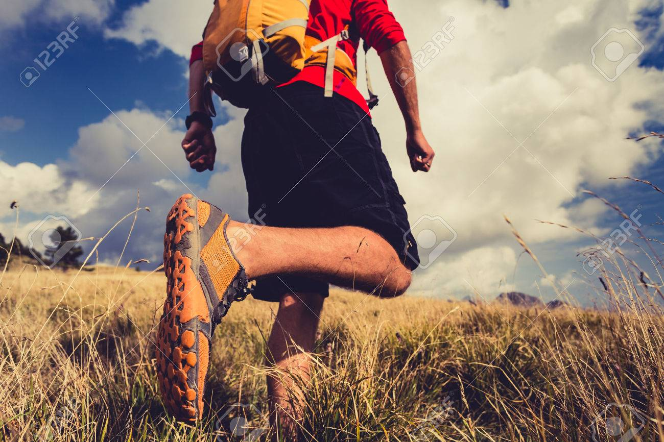 Man hiking or trail runner walking in mountain landscape inspirational. Fitness and healthy lifestyle hiker or trekker walk on dry grass, fall autumn nature. Travel in Italy, Europe. Selective focus on a sports shoe. - 56096680