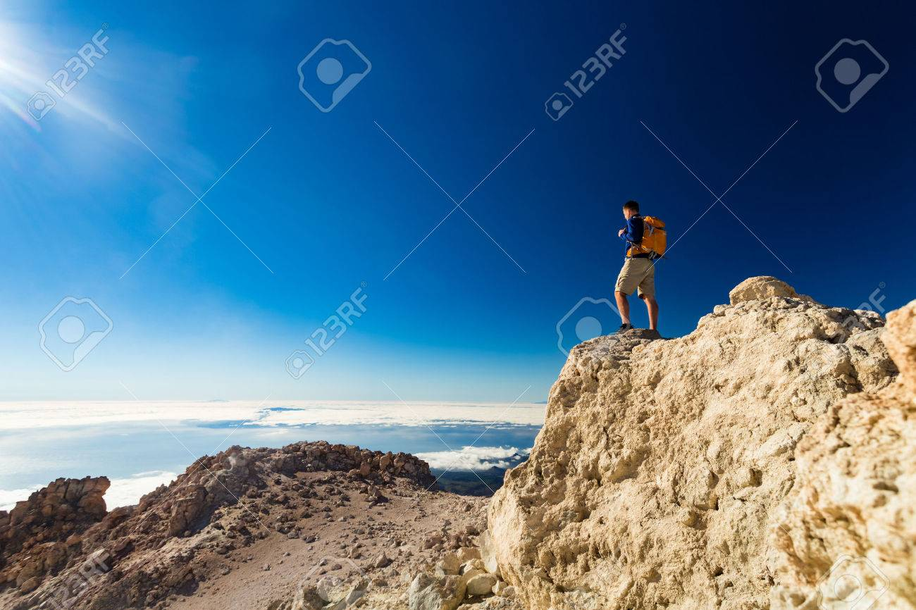 Man tourist hiker or trail runner looking at beautiful inspirational landscape in high mountains. Male runner with backpack, happiness and enjoying inspiring view on rocky top of mountain, Spain. - 57161617