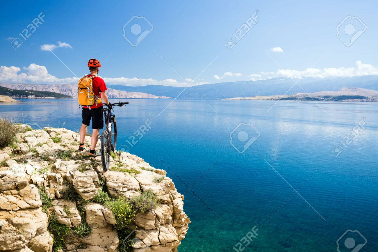Mountain biking rider with bike looking at inspiring sea and mountains landscape. Man cycling MTB on enduro rocky trail path at sea side. Summer sport, training fitness motivation and inspiration. - 58181582