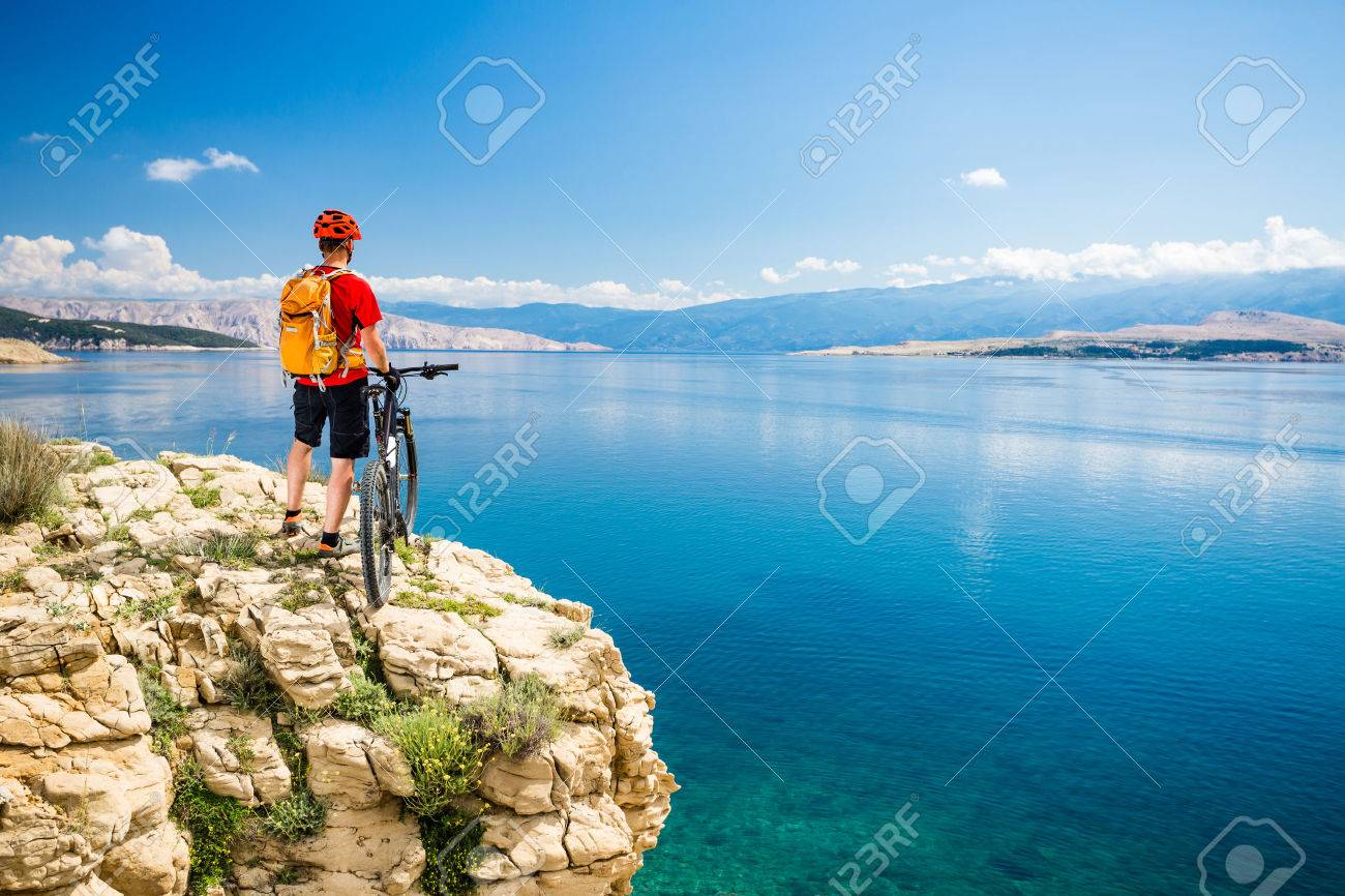 Mountain biker looking at view and traveling on bike in summer sea landscape. Man rider cycling MTB on country road or single track. Fitness motivation, inspiration in beautiful inspirational view. - 58584076