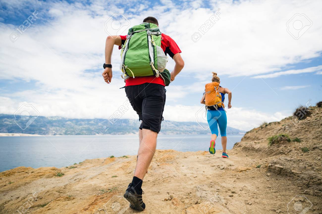 Couple runners running with backpacks on rocky trail at seaside and mountains. Young woman and man trail running on mountain path looking at beautiful inspirational landscape view. - 60121048