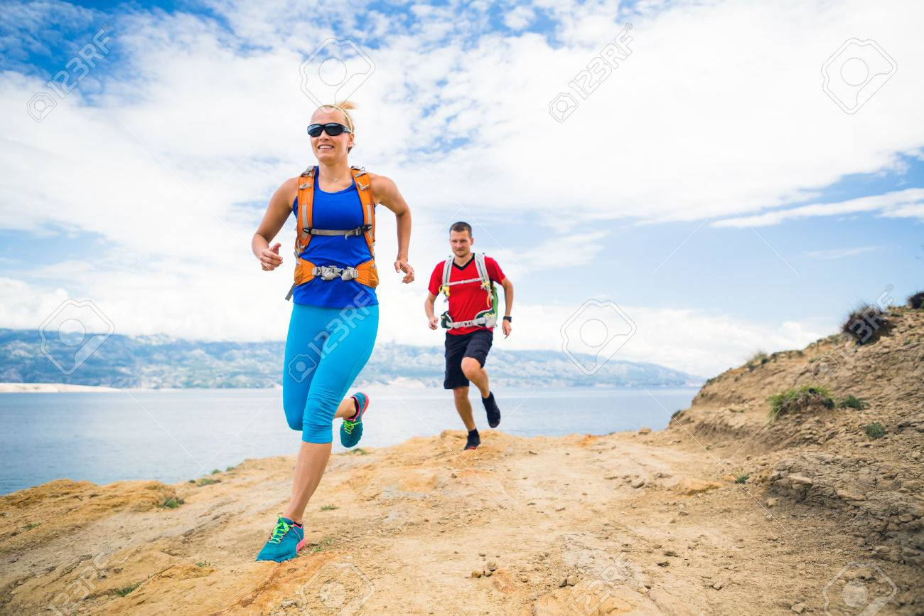 Couple runners running with backpacks on rocky trail at seaside and mountains. Young woman and man trail running on mountain path looking at beautiful inspirational landscape view. - 60121050