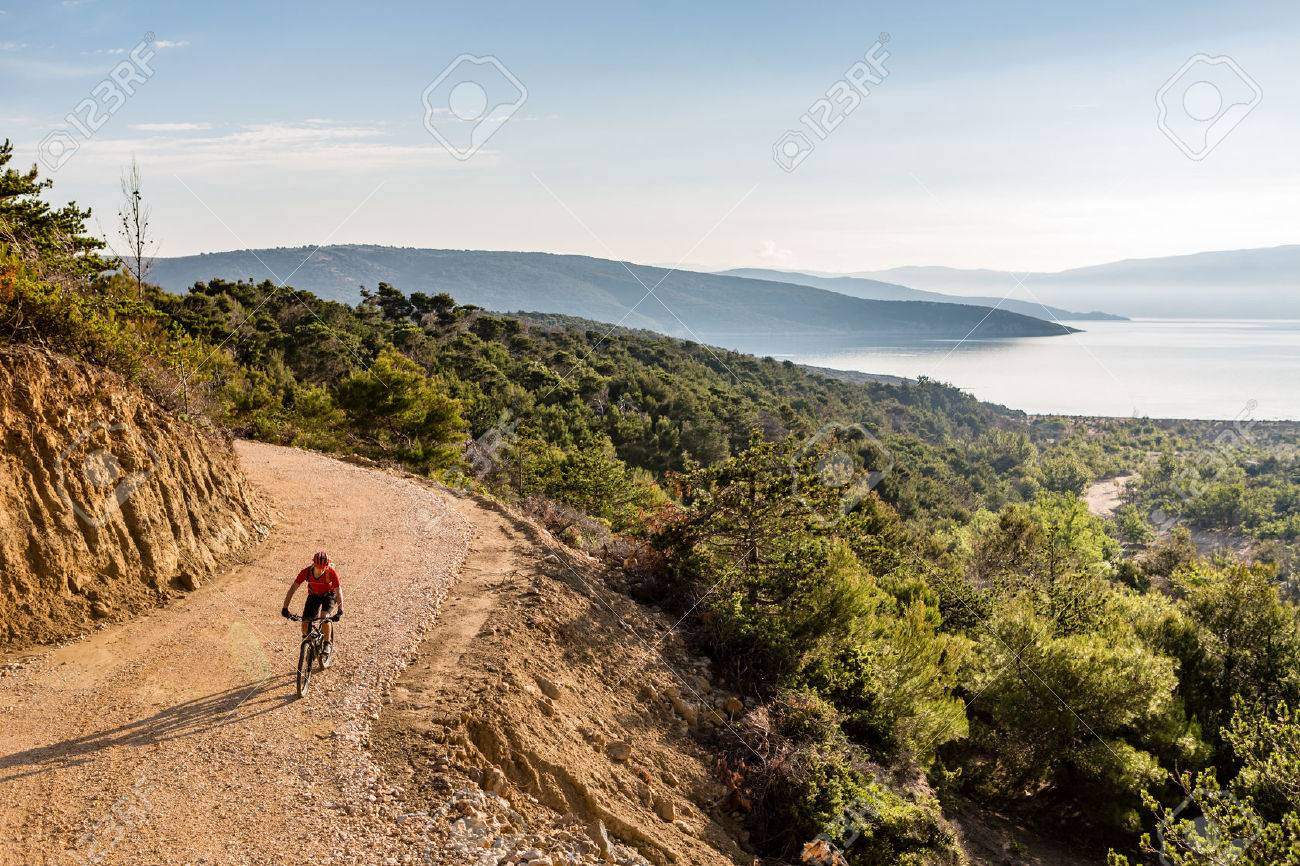 Mountain biker riding on bike in autumn inspirational mountains landscape. Man cycling biking on dirt road, trail track. Sport fitness motivation and inspiration outdoors MTB rider training, Croatia. - 61812328