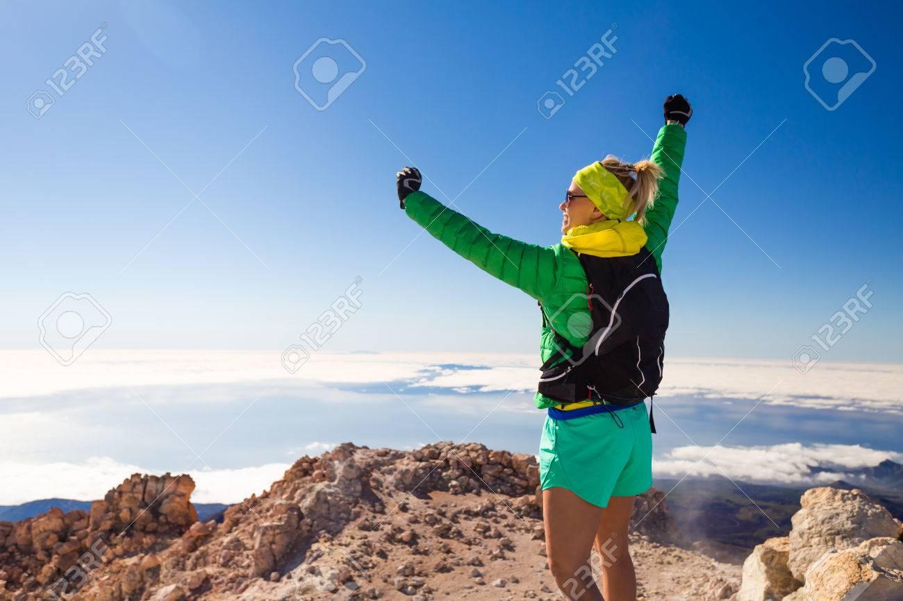 Mujer senderismo escalada exitosa con la mochila en la parte superior de la montaña del Teide, Tenerife. En cuanto a la opinión del paisaje