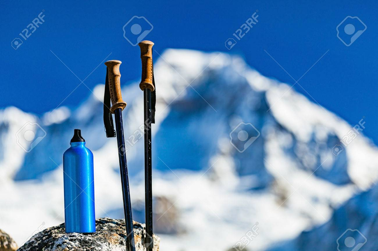 Hiking Gear over Himalaya Mountains Background. Travel Equipment, Trekking Stick and Water Bottle in Inspirational High Himalayas Landscape over Blue Sky in Nepal. - 64040346