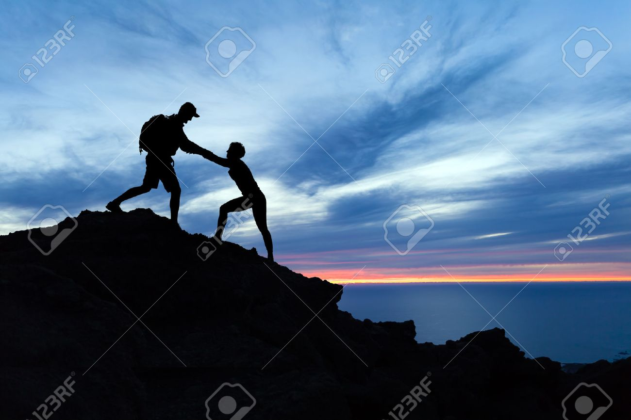 Teamwork couple hiking, help each other, trust assistance and silhouette in mountains, sunset over ocean. Team of climbers man and woman helping hand on mountain top, inspirational climbing team. - 64040362