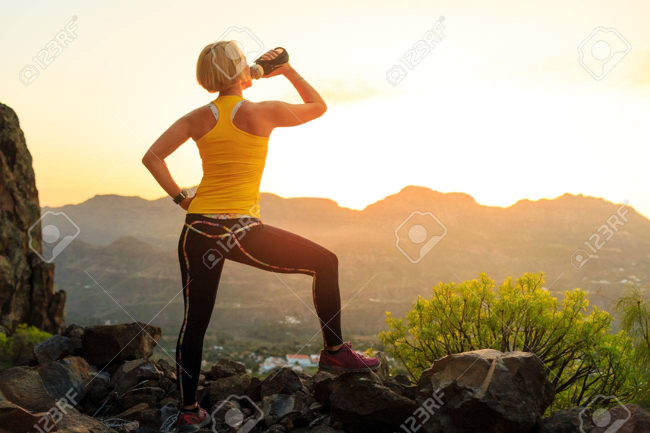 Woman hiking or running in mountains drinking water, sunset on mountain top. Female hiker, climber or trail runner with water bottle, looking at beautiful night sunset inspirational landscape. - 71163713