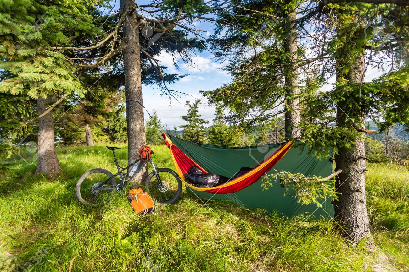 Camping in woods with hammock and sleeping bag on mountain biking adventure trip in green mountains. Travel campsite when mtb cycling with backpack. Lightweight shelter in wilderness forest, Poland. - 83782545