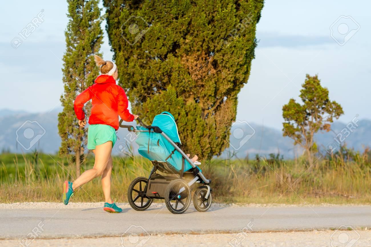 Running mother with child in stroller enjoying motherhood at sunset and mountains landscape. Jogging or power walking woman with pram on at sunset. Beautiful inspirational mountains landscape. - 87052288