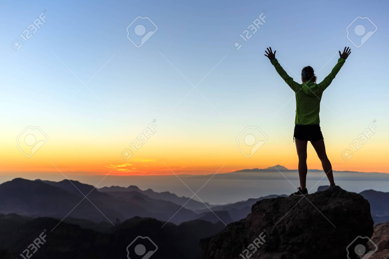 Woman successful hiking or climbing in mountains, motivation and inspiration in beautiful sunset landscape. Female hiker with arms up outstretched on mountain top looking at view. - 147732667