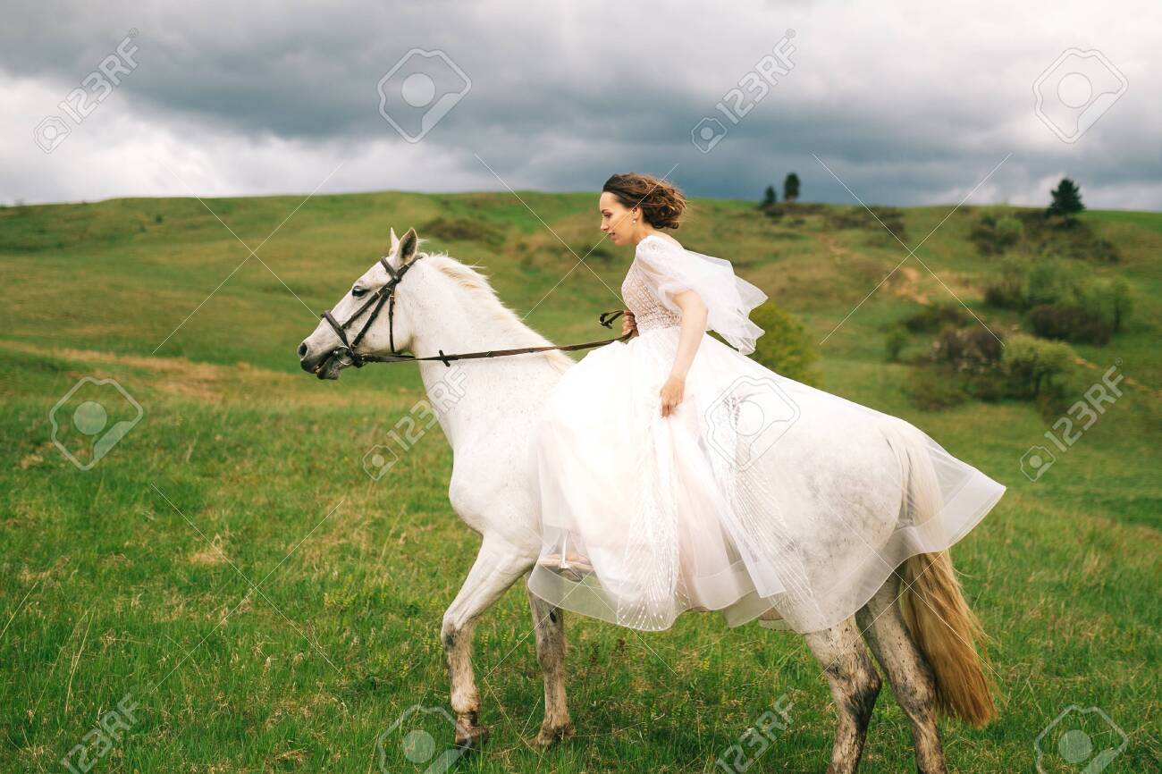 Bride In Wedding Dress Rides A White Horse Stock Photo Picture And Royalty Free Image Image 138028823