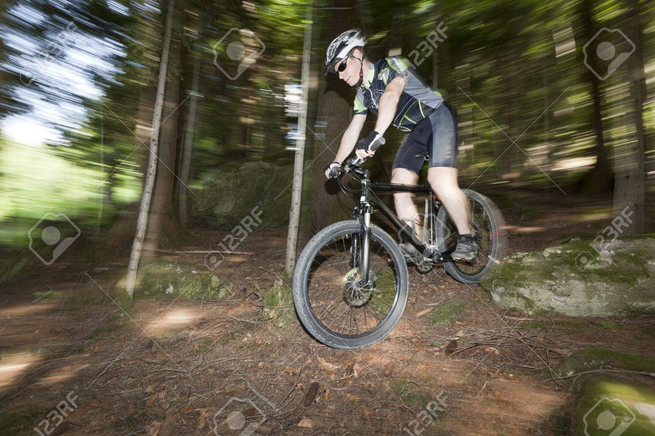 A mountain Biker in a forest. Panning the camera, so background is with motion blur. Stock Photo - 7671834