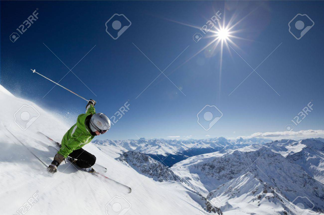 Female skier on downhill race with sun and mountain view. - 7671830