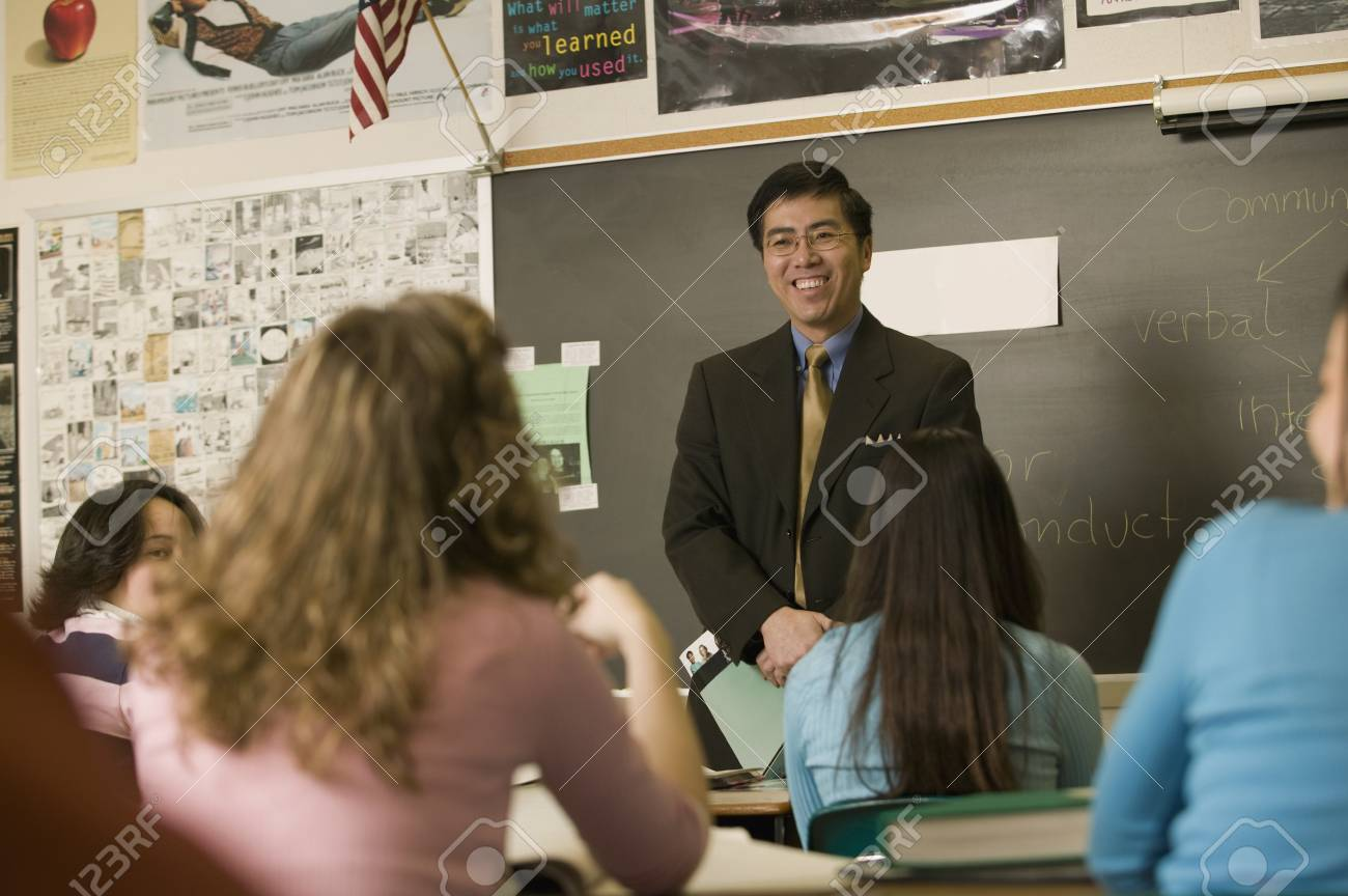 asian teacher talking to students in classroom stock photo picture
