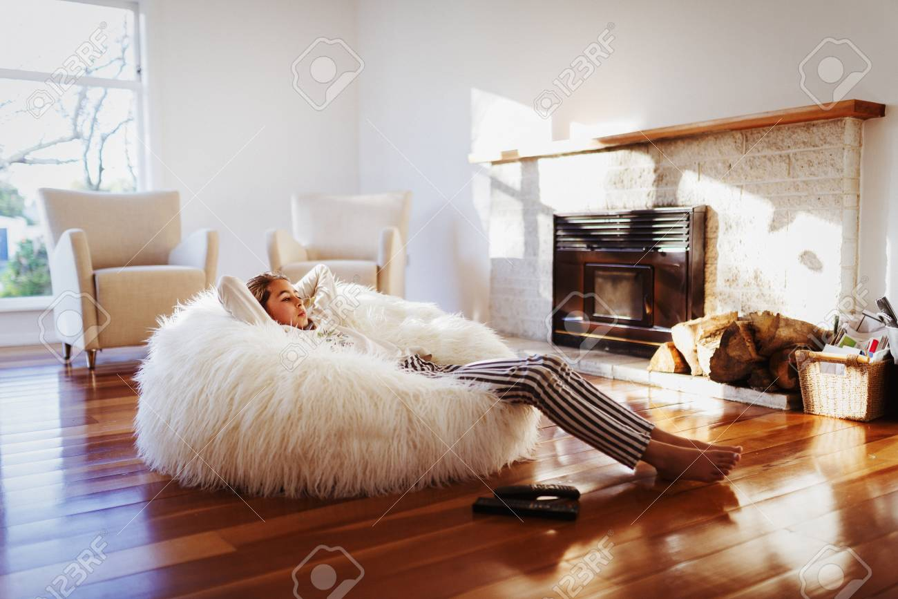Mixed Race Girl Relaxing In Beanbag Chair In Living Room Stock Photo    92960473