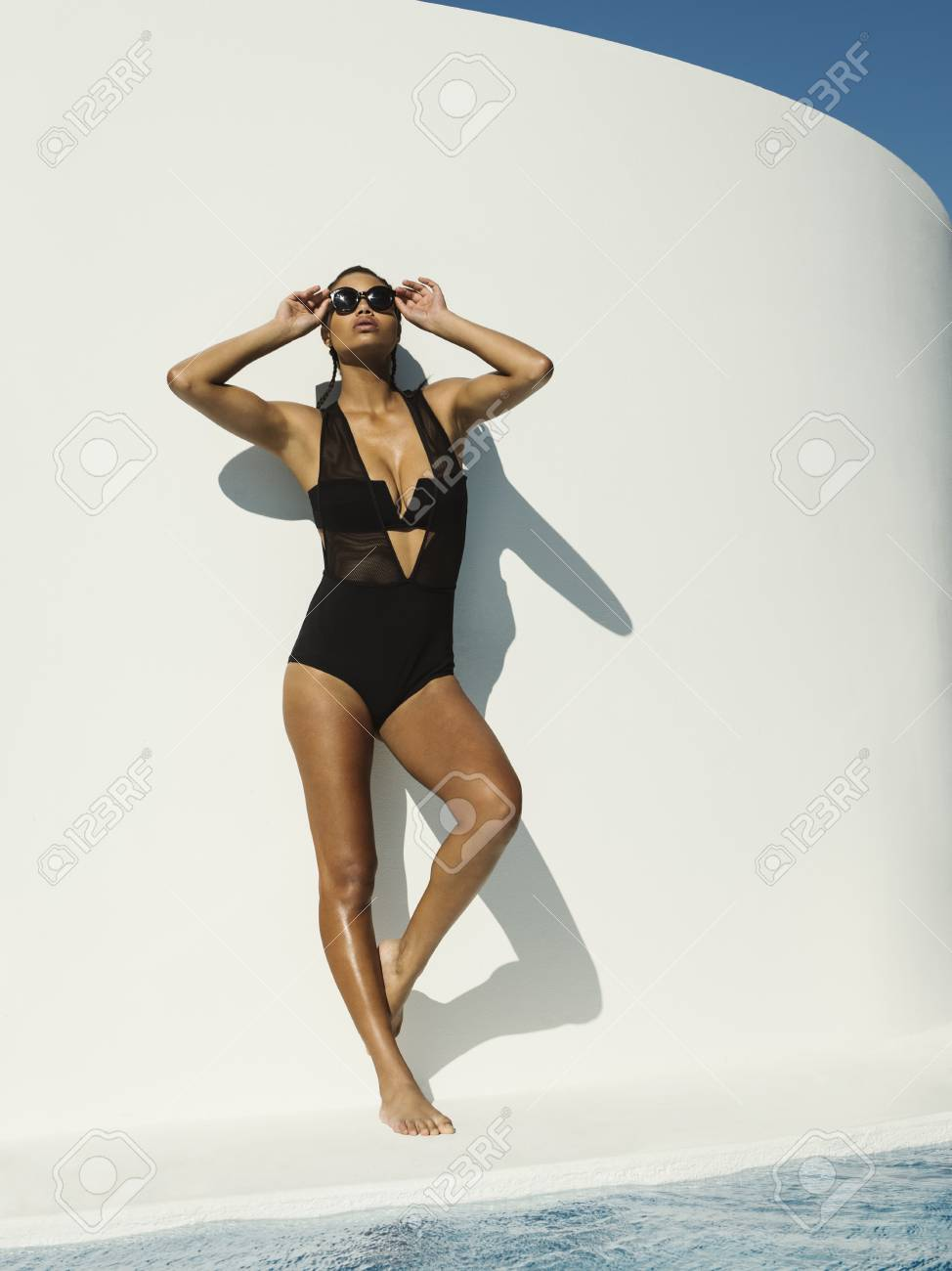 4a64adf1087 Mixed Race Woman In Swimsuit Wearing Sunglasses Near Swimming Pool Stock  Photo - 93091965
