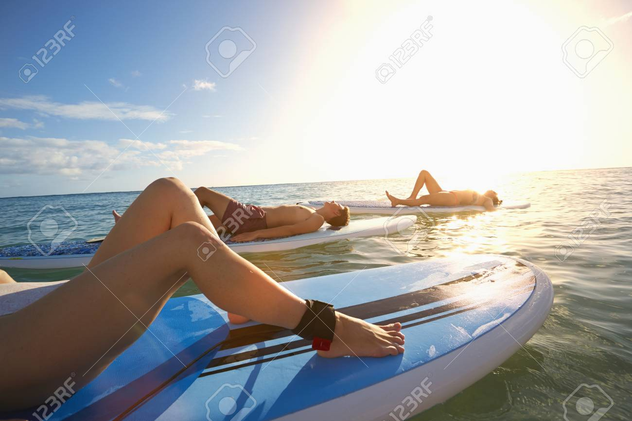 Friends Laying On Paddle Boards In Ocean Stock Photo   95488442