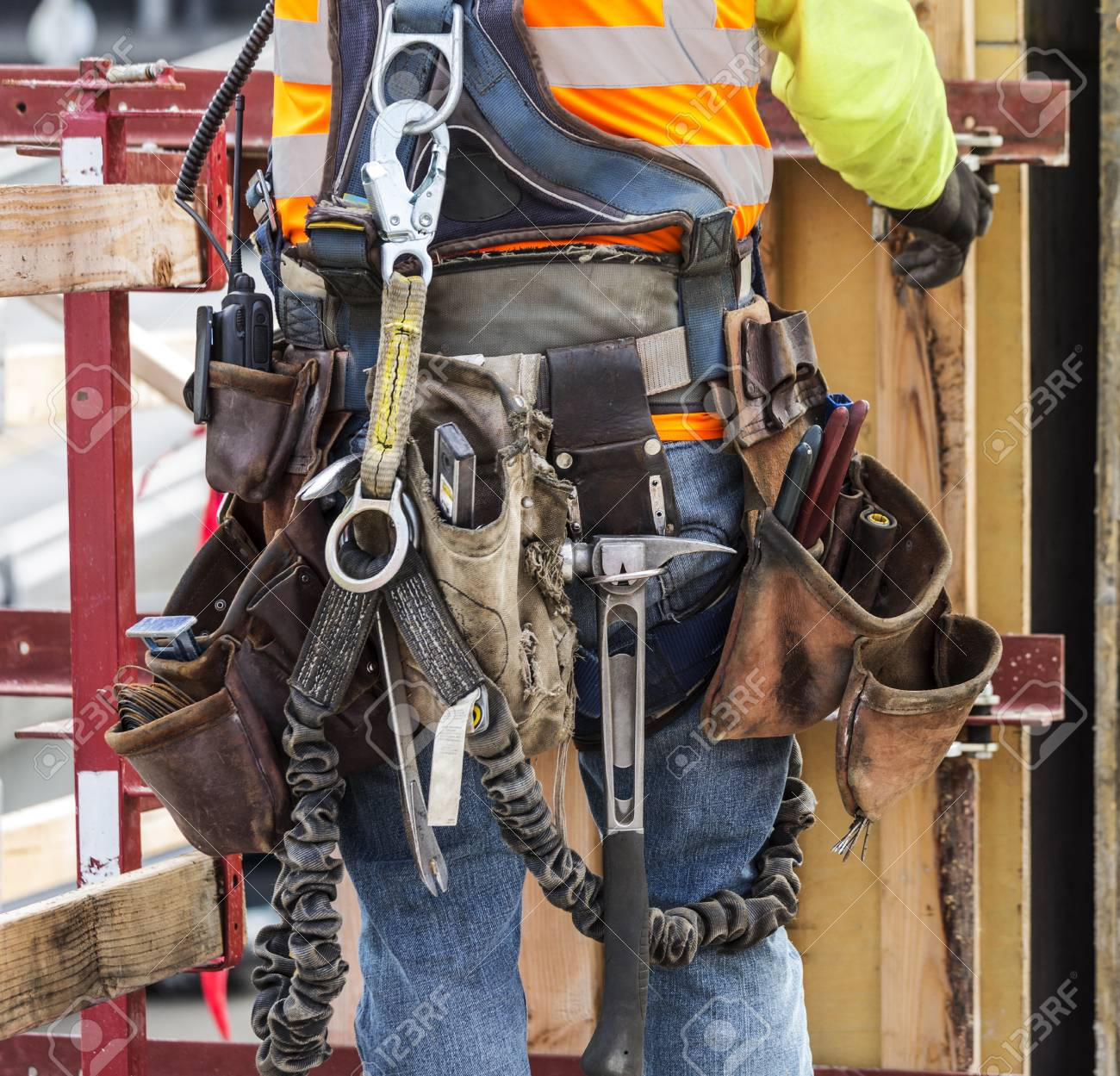 97169767 hispanic worker wearing tool belt at construction site hispanic worker wearing tool belt at construction site stock photo