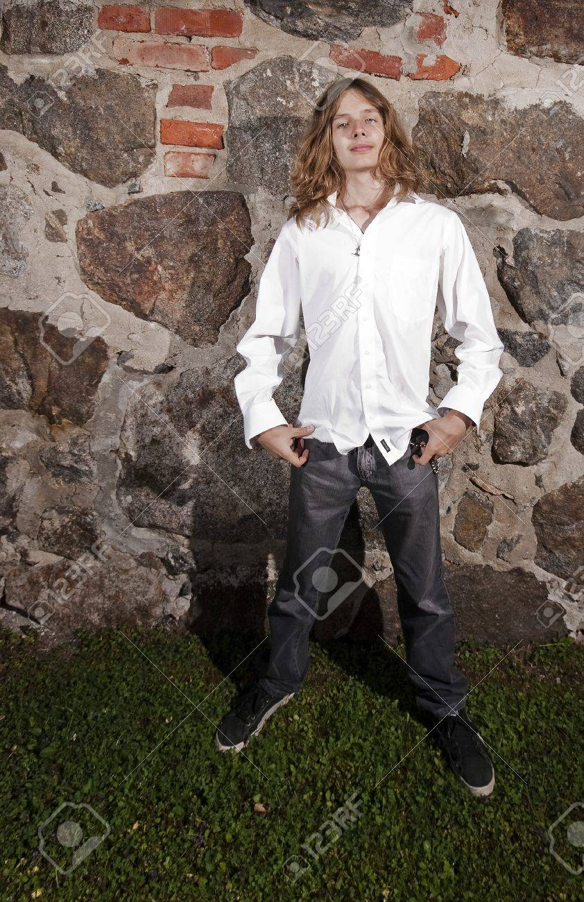 Teenage male model with long hair posing in front of a rock wall. Stock Photo - 8113336