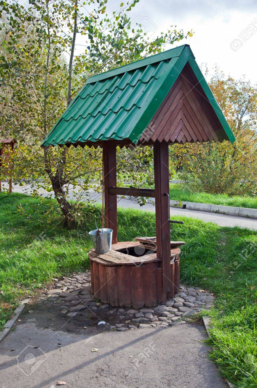 Countryside water well with a bucket. - 12049773