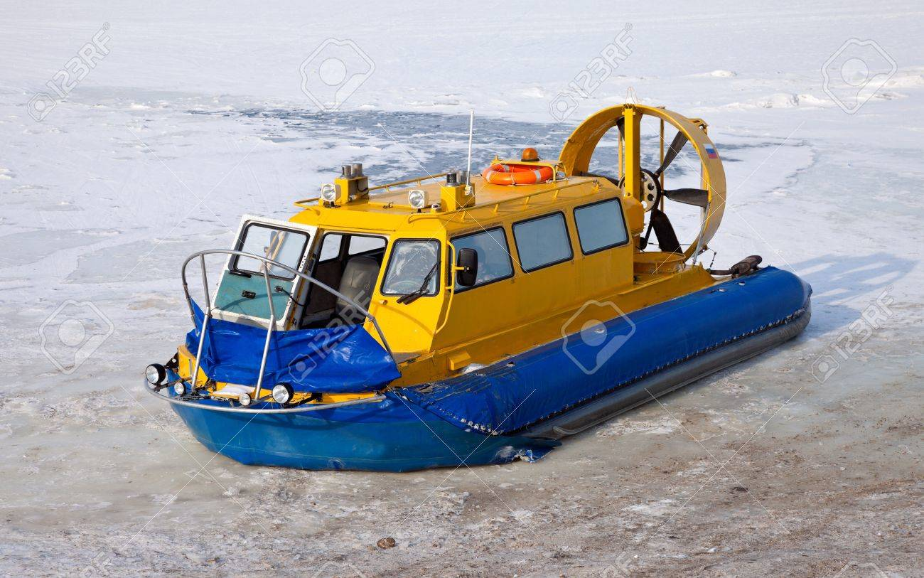 Hovercraft on the bank of a frozen river - 12514792