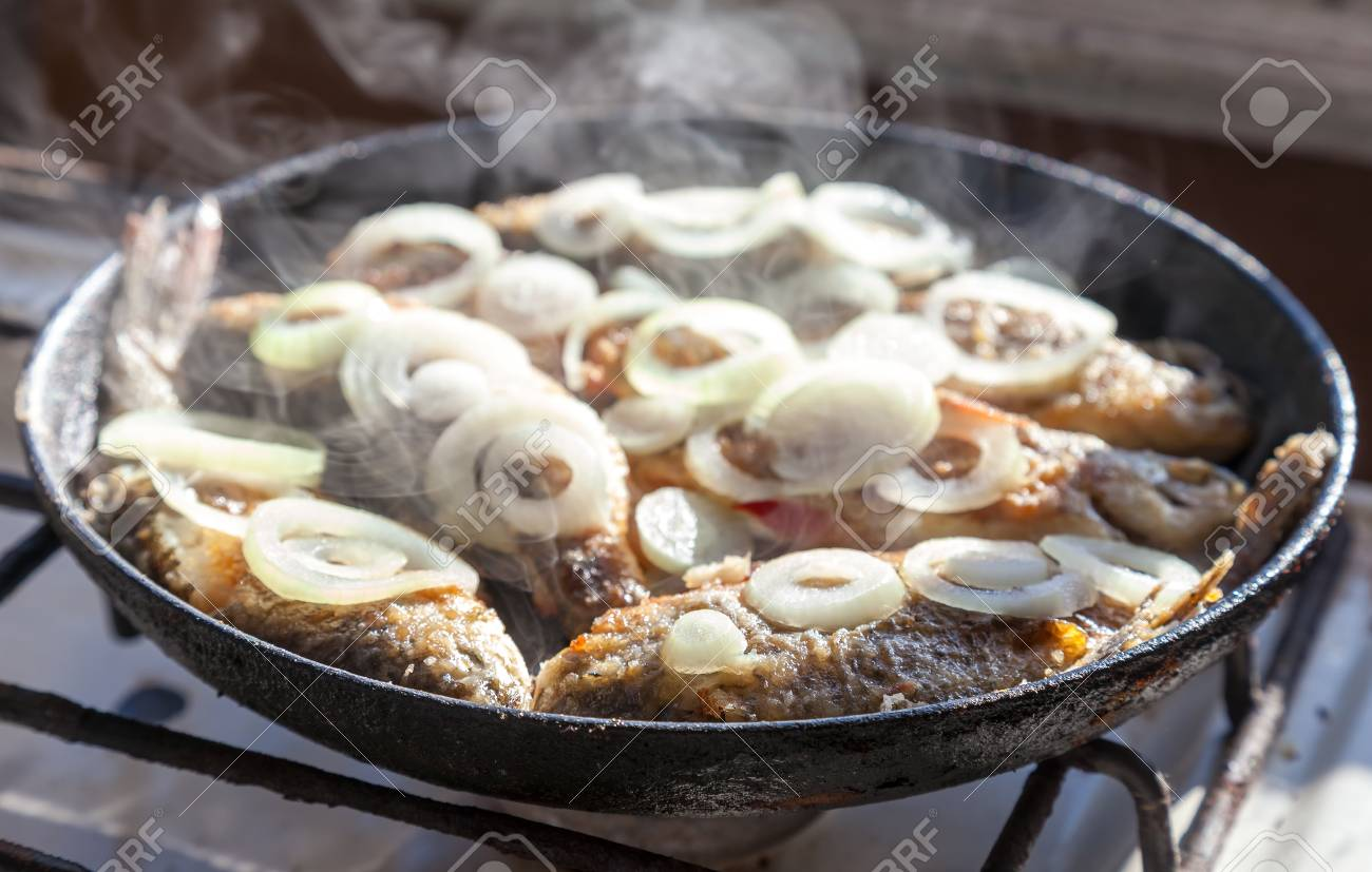 Fried fish in the old frying pan Stock Photo - 22257235