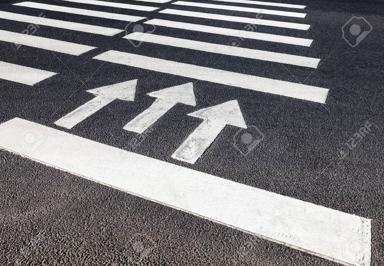 Zebra crossing with white marking lines and direction of motion on asphalt - 47724696