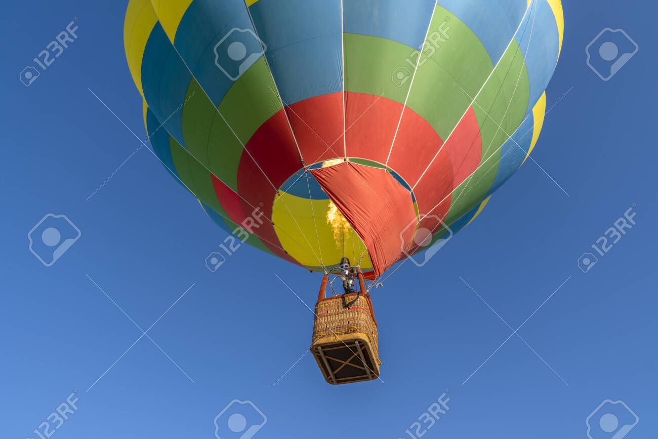 Detail of colorful hot air balloon heading up in blue sky. Close up. - 148310324