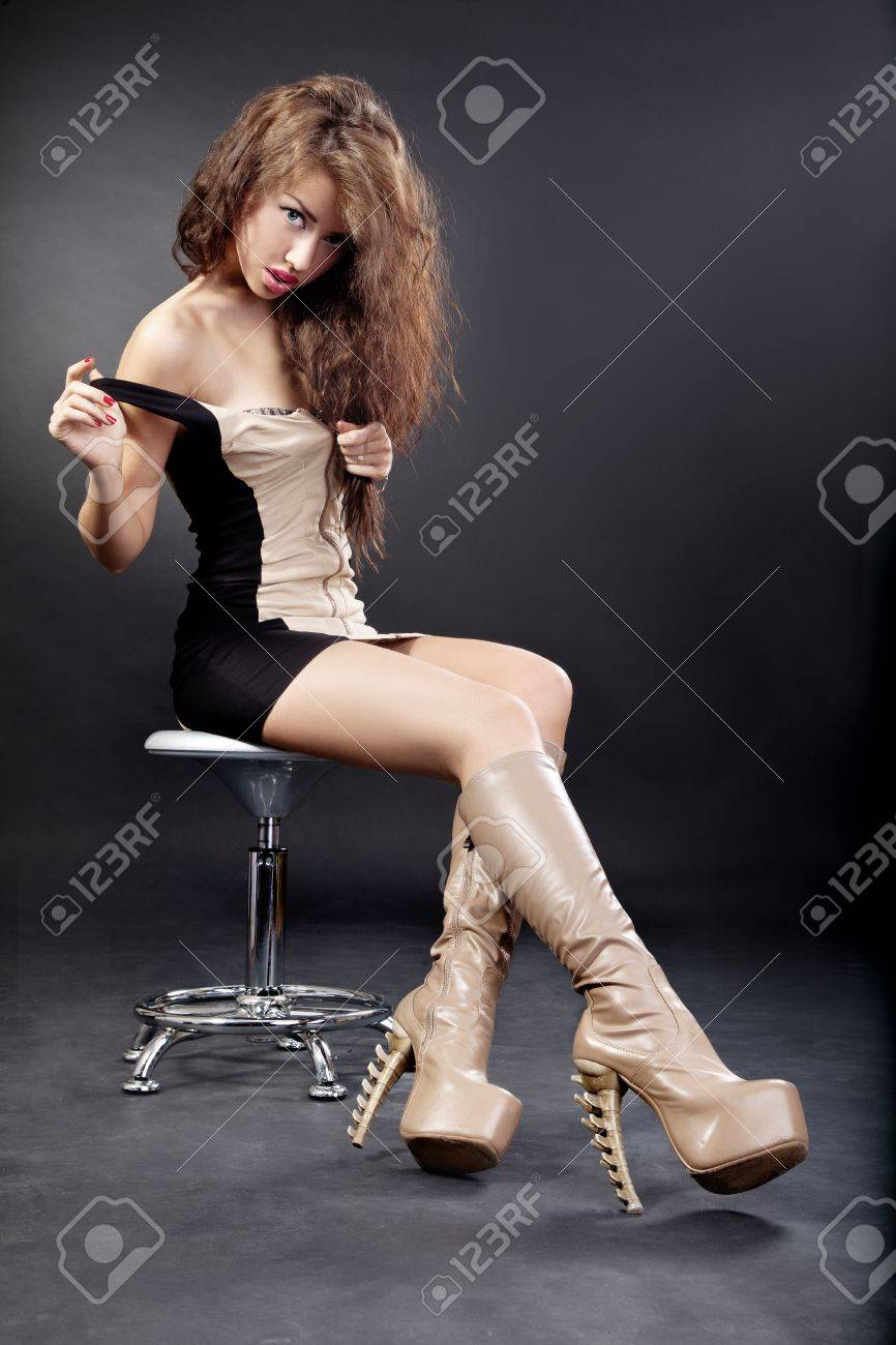 Beautiful young woman wearing boots. Image isolated against black background. Stock Photo - 13858438