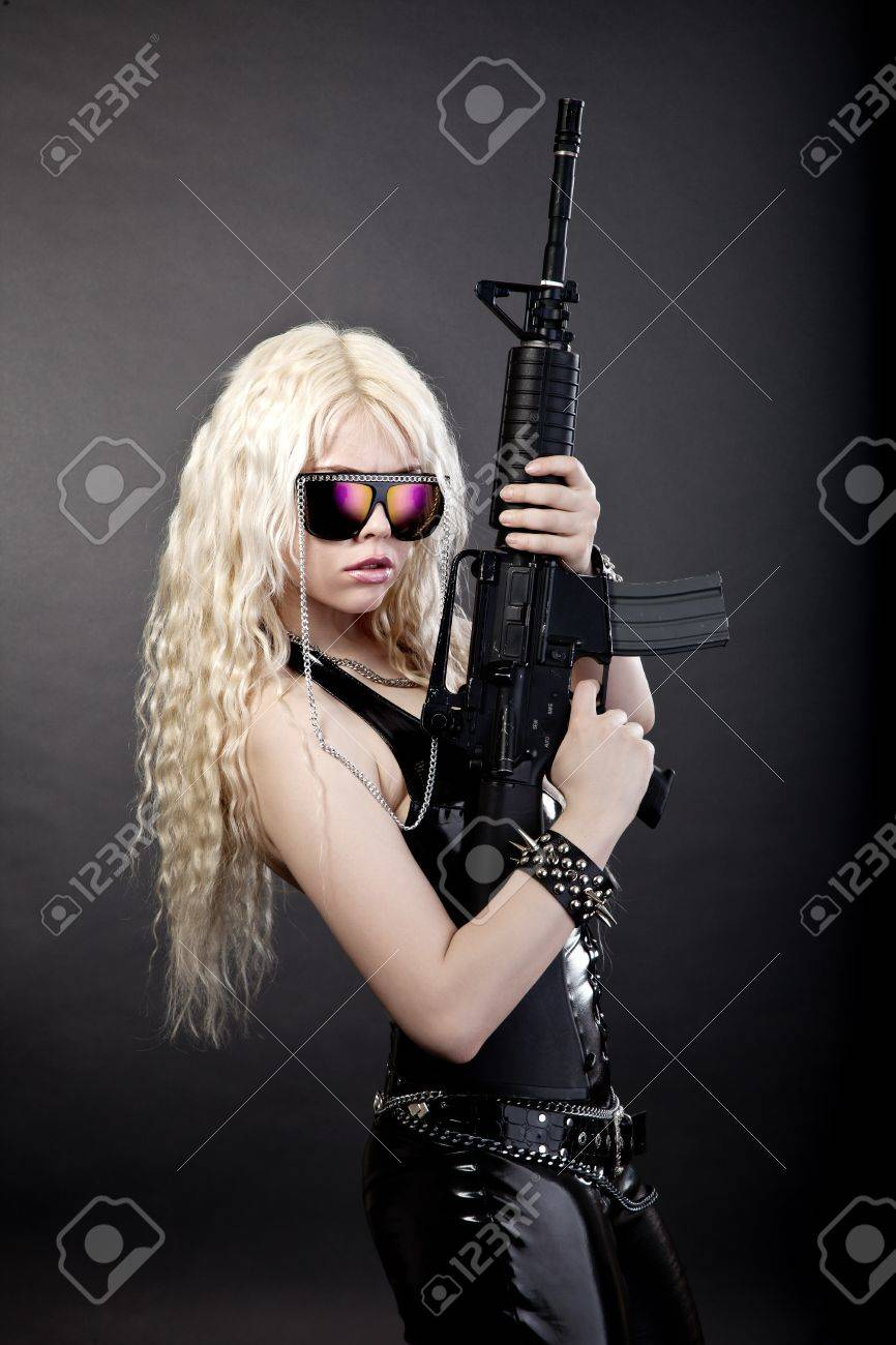 Beautiful sexy girl with a rifle isolated on black background Stock Photo - 13858415