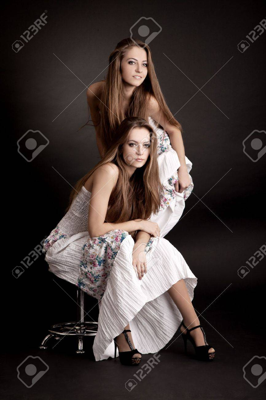 Two beautiful girls twins, isolated on the grey background Stock Photo - 13911223