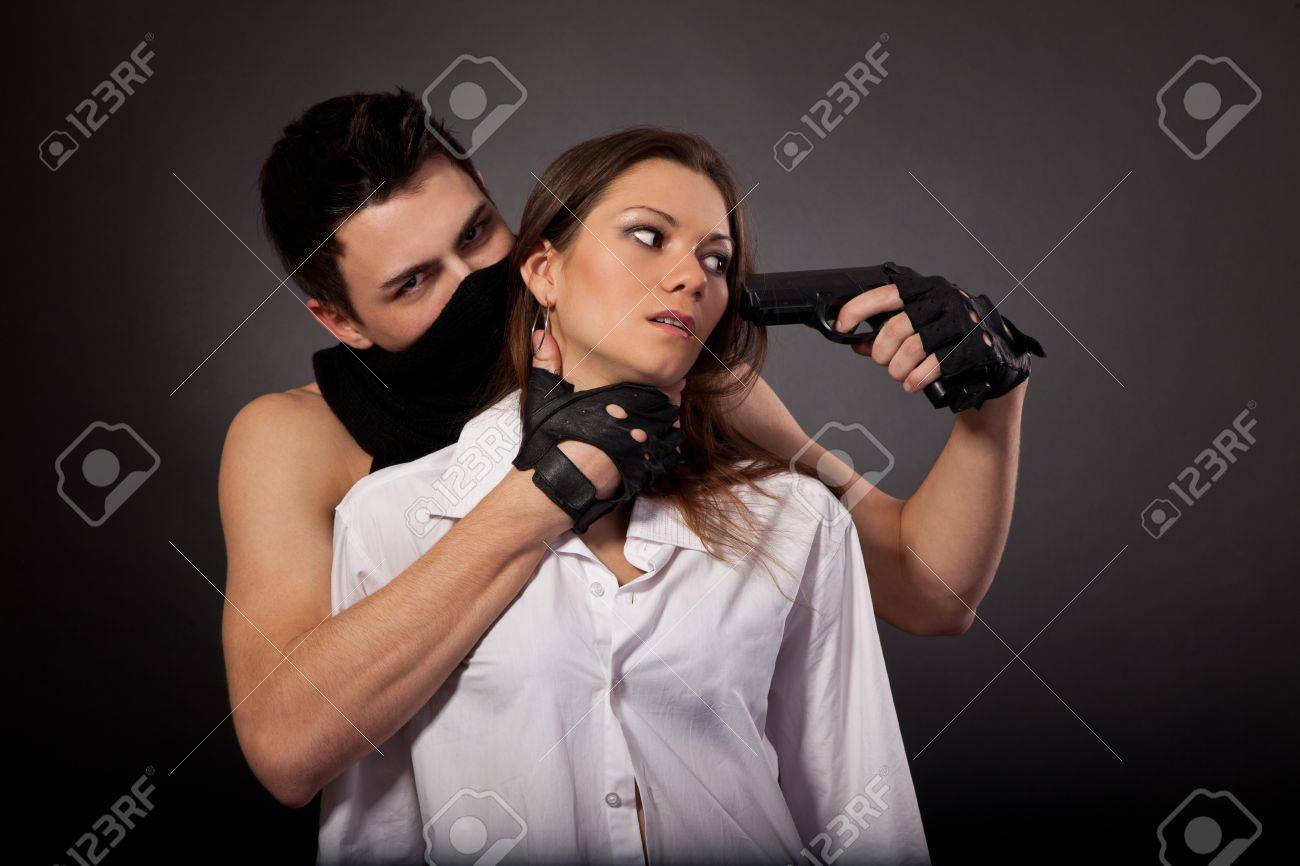 Man take a beautiful woman as a hostage isolated on a white background Stock Photo - 13911219