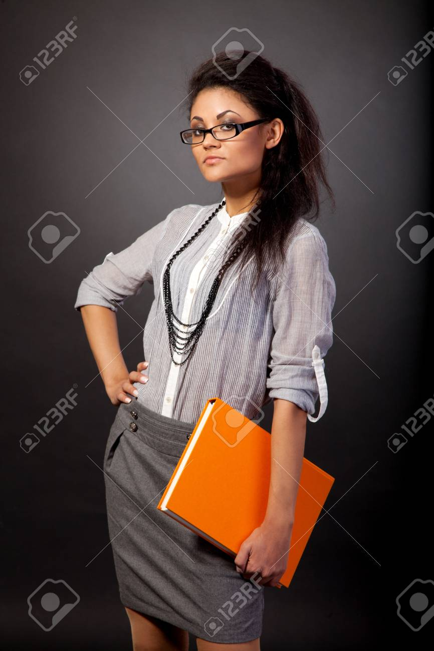 Beautiful student girl is holding an orange book isolated on black Stock Photo - 13911231