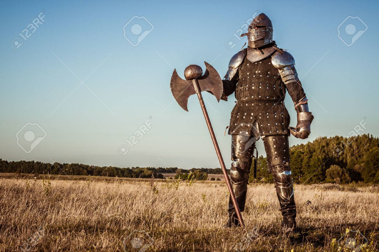 Medieval knight in the field with an axe - 22199969