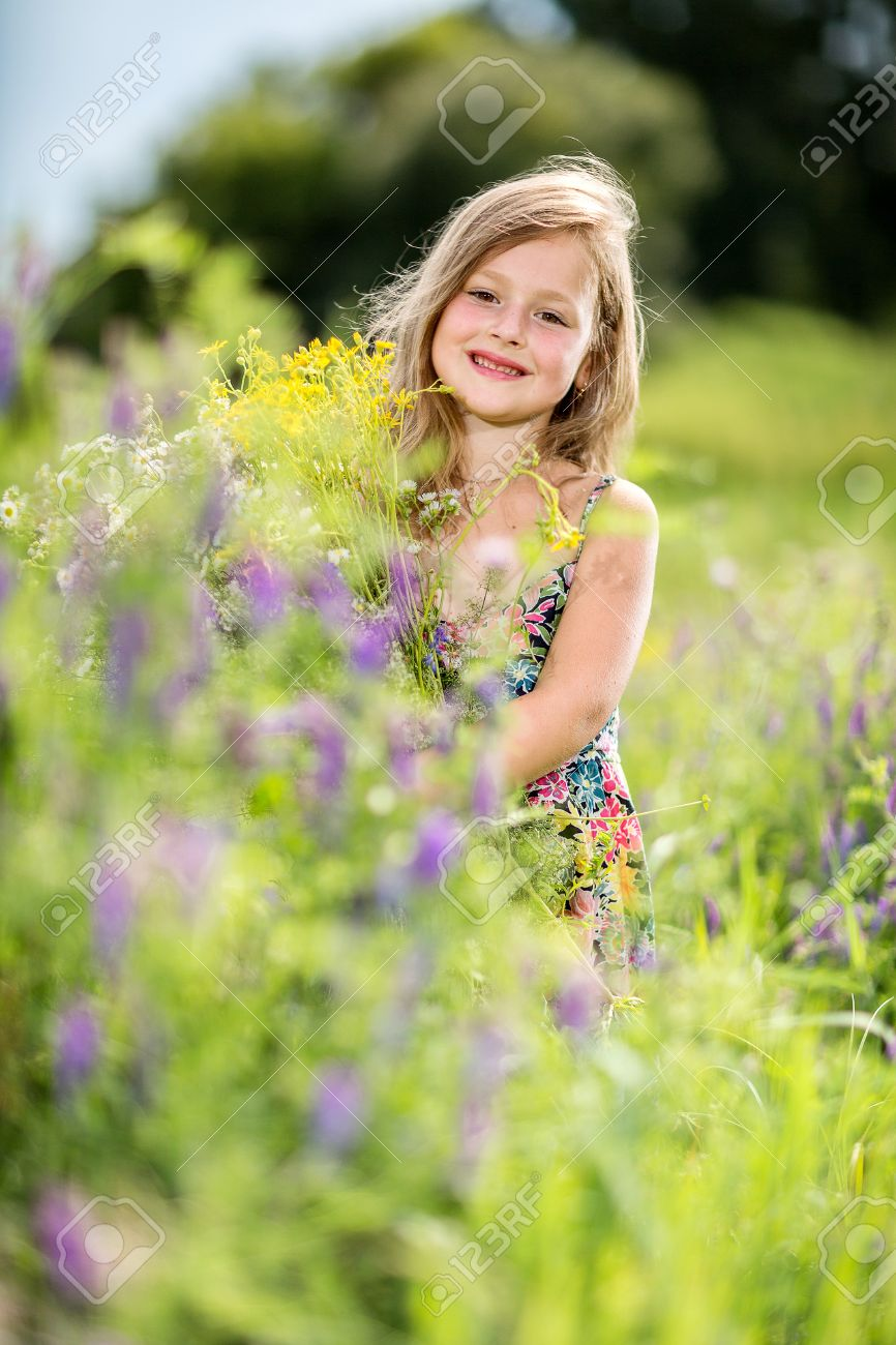 happy baby girl playing outdoor, cute child holding fresh sunflower