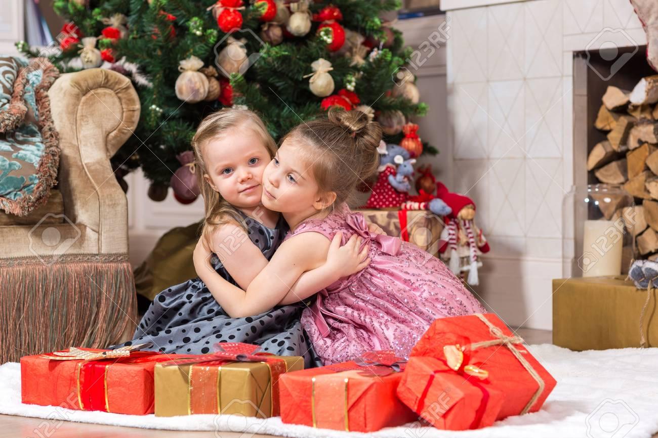 Zwei Nette Kleine Mädchen Mit Weihnachtsgeschenk Unter Dem ...