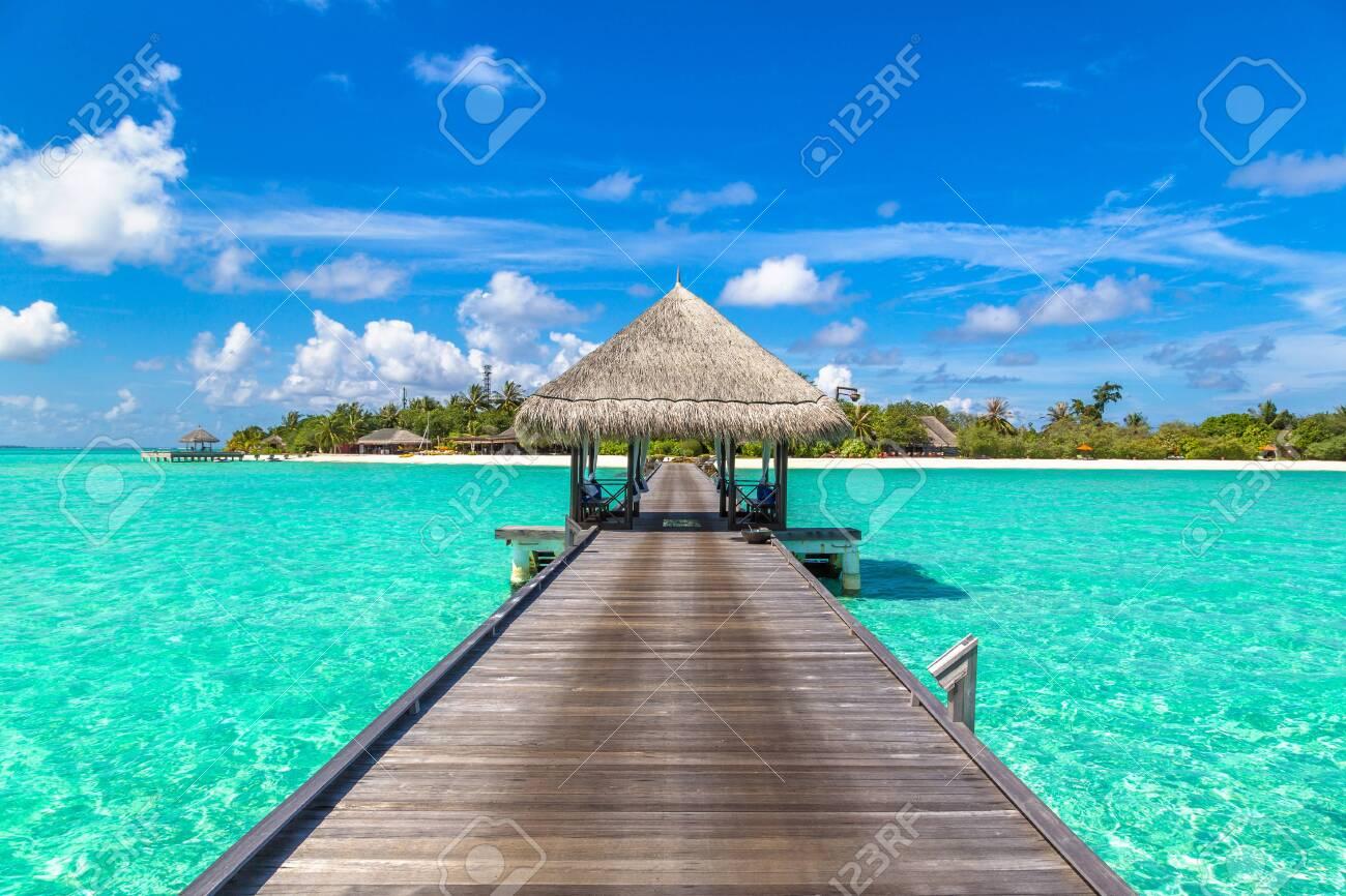 MALDIVES - JUNE 24, 2018: Water Villas (Bungalows) and wooden bridge at Tropical beach in the Maldives at summer day - 123059809