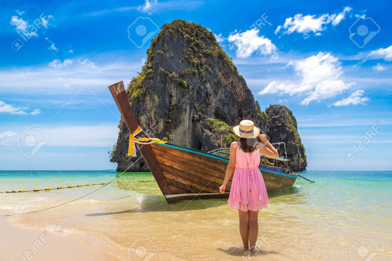 Beautiful tourist woman near traditional longtail boat in Phra Nang Beach, Thailand - 173329231